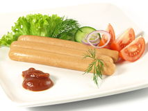 Frankfurters with ketchup and vegetables. Frankfurters on a plate on isolated background Royalty Free Stock Image