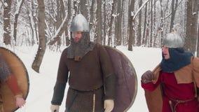 Frankish medieval, irlandés, guerreros de vikingo en armadura que caminan en un bosque del invierno con los escudos de las espada metrajes