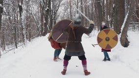 Frankish medieval, irlandés, guerreros de vikingo en armadura que luchan en un bosque del invierno con los escudos de las espadas metrajes