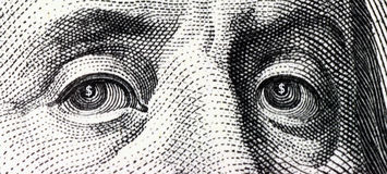 Franklin. Close-up face of Benjamin Franklin, in whose eyes see the dollar sign royalty free stock photography