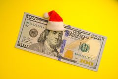 Franklin prezydent w czerwonym Święty Mikołaj kapeluszu na 100 dolara amerykańskiego rachunku na jaskrawym żółtym tle Pojęcie kos zdjęcie stock