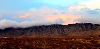 The Franklins. Photo of the Franklin Mountains in El Paso, TX. Rain was coming from the other side and the clouds were creeping over the peaks. These mountains stock image