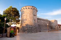 Frankopan fortress tower walls and little wooden shop at Krk - C Royalty Free Stock Photography