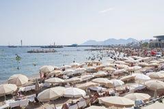 FRANKREICH, CANNES - 6. AUGUST 2013: Leute entspannen sich auf dem Strand durin Stockbilder