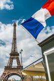 Frankreich-Flagge über blauem bewölktem Himmel und Eiffelturm in Paris Lizenzfreies Stockfoto