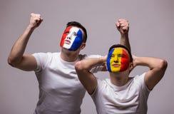 Frankreich gegen Rumänien auf weißem Hintergrund Fußballfane von Rumänien- und Frankreich-Nationalmannschaften zeigen Gefühle Stockfotos