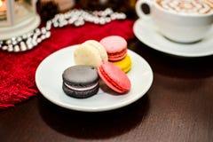 Frankrike efterrättmakron och koppcappuccino på tabellen i kafé Royaltyfri Foto