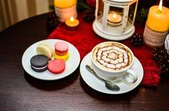 Frankrike efterrättmakron och koppcappuccino på tabellen i kafé Arkivfoto