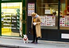 Frankrike Paris, Augusti 6, 2017: Kvinna med en hund på gatan med matköp arkivbild