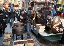 Frankrike/Strasbourg - 20 11 2014: Kastanjer för folkfolkköp på julmarknaden royaltyfria bilder