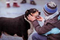 Frankt ögonblick med en ung pojke som daltar en manlig gammal hund arkivfoton