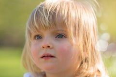 Frankt allvarligt tänka eller det ledsna barnet behandla som ett barn caucasian blonda den utomhus- flickaståenden arkivbilder