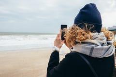 Frankt foto av hipsterflickahandelsresanden på sandkust på vintern arkivfoto