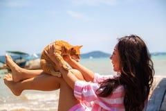 Frankt foto f?r atmosf?risk livsstil av den unga h?rliga asiatiska kvinnan p? semesterlekar med en katt arkivfoton
