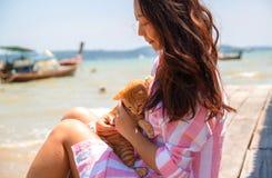 Frankt foto f?r atmosf?risk livsstil av den unga h?rliga asiatiska kvinnan p? semesterlekar med en katt royaltyfri bild