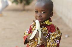 Frankt skott av afrikansvartpojken som äter den utomhus- bananen arkivfoto