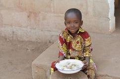 Frankt skott av den lilla pojken för svart afrikan som utomhus äter ris royaltyfri bild