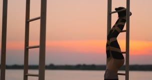 Frankt skott av den verkliga sunda och färdiga kvinnan som utför hängande benlönelyfter på utomhus- konditionstation i solnedgång arkivfilmer