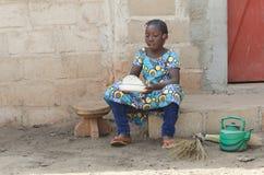 Frankt skott av ris för matlagning för afrikansvartflicka utomhus arkivfoto
