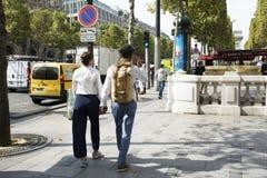 Frans mensenvriend en meisje die hand in hand op gang bij stoep in L'avenue des Champs-Elysees lopen royalty-vrije stock fotografie