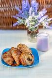 Franse croissants, broodjes met rozijnen en bosbessenyoghurt in glaskruiken op een lijst stock afbeelding