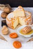 Franse of Duitse zachte kaas van camemberttype met oranje schil, honingsdipper, droge vruchten, mes royalty-vrije stock afbeeldingen