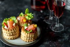 Franse keuken, knapperige pasteitjes met sla en gerookte zalm naast een glas rode wijn royalty-vrije stock foto's