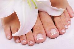 Franse pedicure op vrouwelijke voeten Stock Foto's