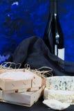Franse rode wijn en zachte kazen op zwarte steenschotel stock afbeeldingen