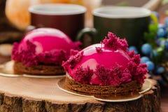 Fransk bakelse med rosa färger glasar och den burgundy sockerkakan Arkivfoto