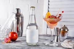 Fransk daiquiri, alkoholcoctail med ny apelsin- och grapefruktfruktsaft med en flaska av uppiggningsmedel och ett ställe under Fotografering för Bildbyråer