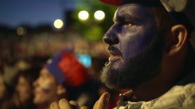 Fransk fan med målarfärgframsidan som oroas mot bakgrundsfolkmassan från förlust hans lag lager videofilmer