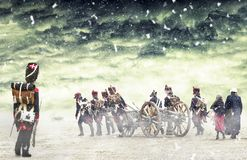 Fransk grenadjär som håller ögonen på napoleonic soldater och kvinnor som marscherar och drar en kanon i vanligt land, bygd med Royaltyfria Foton