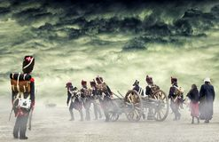 Fransk grenadjär som håller ögonen på napoleonic soldater och kvinnor som marscherar och drar en kanon i vanligt land, bygd med d Royaltyfri Bild