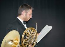 fransk horn Handtag av ett musikinstrument i händerna av ett rogant Man i dräkt och fjäril med musikinstrumentet royaltyfri foto