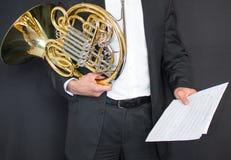 fransk horn Handtag av ett musikinstrument i händerna av ett rogant Man i dräkt och fjäril med musikinstrumentet royaltyfria bilder