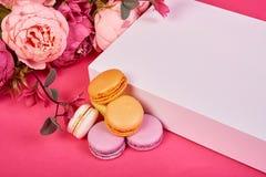 Fransk makronkaka Makron i ask med blommor på rosa den lekmanna- bakgrundslägenheten arkivfoto