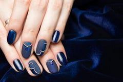 Fransk manikyr - härliga manicured kvinnliga händer med blå manikyr med bergkristaller på mörker - blå bakgrund royaltyfria bilder