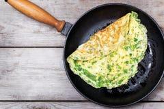 Fransk omelett med örter som lagas mat i gjutjärnkastrull arkivfoton