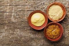 Fransk senap, dijon senap och pulver på trälantlig bakgrund från över olika setkryddor royaltyfri fotografi