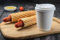 Fransk varmkorv och kaffe på trätabellen royaltyfria bilder