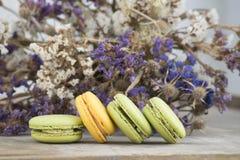 Franska efterrättmacarons med blomman Arkivfoto