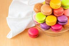 Franska färgrika macarons i en glass kaka står Arkivbild
