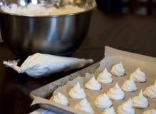 Franska marängkakor på en rostig panna, bakelsepåse och kromplastbunke Royaltyfria Bilder