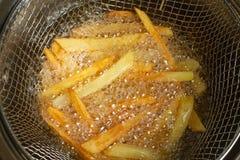 Franska småfiskar för pommes frites, i att koka olja stekte potatisar Fet och smaklig mat Skjutit i en studio royaltyfri fotografi