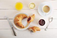 Franskan frukosterar - gifflet, sitter fast, breder smör på, orange fruktsaft och coff Arkivbilder