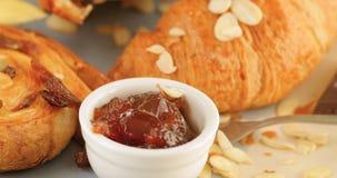 Franskan frukosterar med oranjedriftstoppmarmelad i förgrunden Arkivfoton