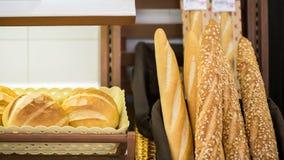Franskan utformar bröd förläggas på hyllorna av supermarket Royaltyfria Bilder