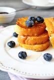 Franskt rostat bröd med blåbär på en vit platta Arkivbilder