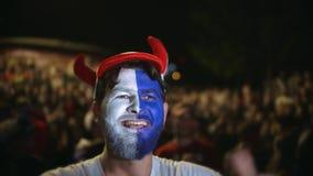 Fransmanfanskriet jublar det favorit- laget för målet som hoppar vänbakgrundfolkmassan lager videofilmer